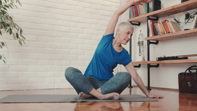 Mature woman doing relaxation exercises at home. video