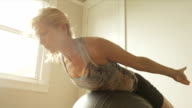 A mature woman doing situps with an exercise ball in her home gym. video