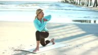 Mature woman doing yoga exercises on the beach video