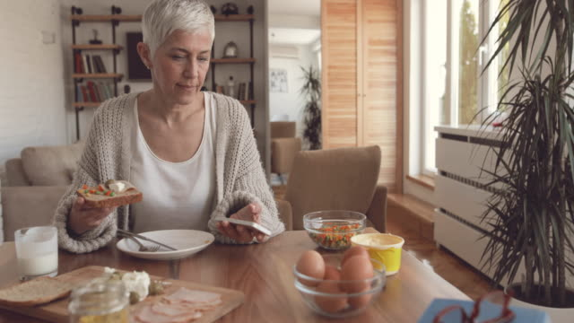Mature woman eating breakfast and reading text message on mobile phone. video