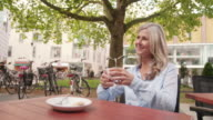 Mature woman enjoying a cup of coffee at a cafe video