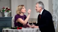 Mature woman feeding man with grapes at restaurant video
