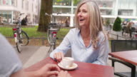 Mature woman having a cup of coffee outdoors with guy video