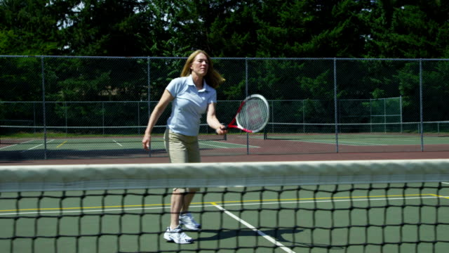 Mature woman hits tennis ball, slow motion video
