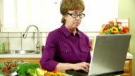 mature woman in kitchen using laptop smiles at camera video
