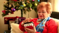 Mature woman opening gift disappointed and unhappy, video