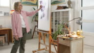 Mature woman painting in cool bohemian home studio video