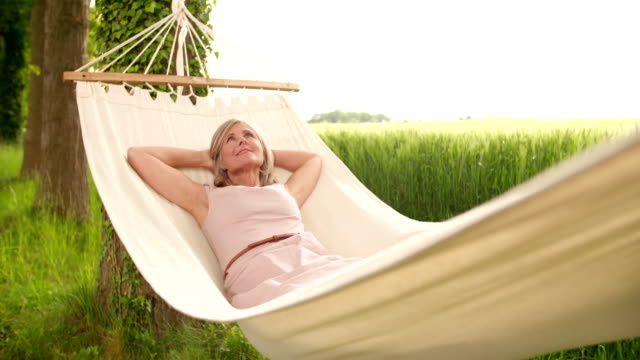 Mature woman relaxing and daydreaming outdoors video