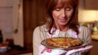 Mature woman smelling a pie she has just cooked video
