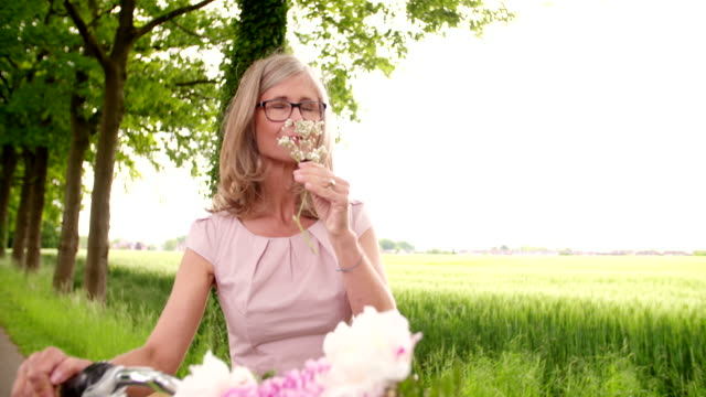 Mature woman smelling flowers in a park with her bicycle video