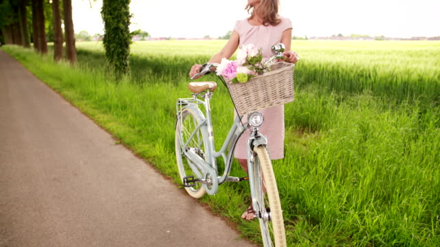 Mature woman standing with a vintage bicycle in a park video