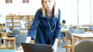 Mature woman walking into focus to study at computer in college library video