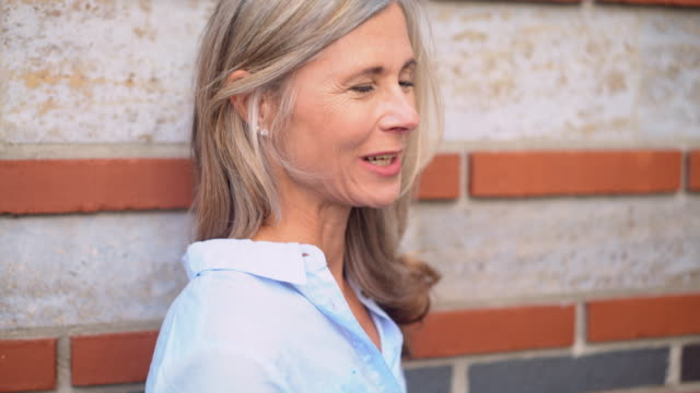 Mature woman with grey hair on a city street smiling video