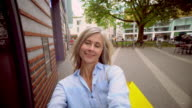 Mature woman with grey hair taking a selfie on a city street video