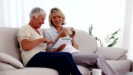 Mature women using tablet pc on the couch video