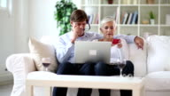 Mature-senior couple shopping over internet with credit card video
