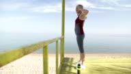 Mature-senior woman exercise beside the sea video