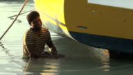 Mauritian young boy cleaning his boat in the lagoon video
