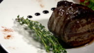 Meat and a sprig of thyme on a white plate video