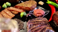 Meat products. variety of smoked meats on a black reflection board video