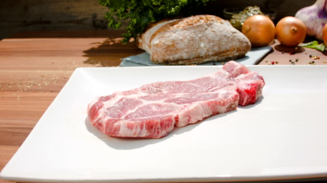 Meat steaks are placed on a board video