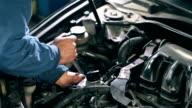 Mechanic fastens detail of car engine video