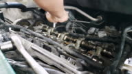 Mechanic fixing cylinder head with camshaft of car engine with socket wrench video