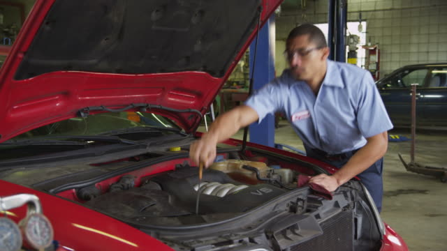 Mechanic in auto repair shop checking oil levels video