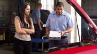 Mechanic in auto repair shop helps customer video