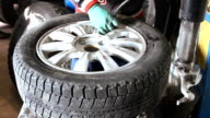 Mechanic inflating car tire closeup video