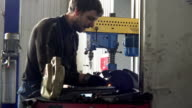 Mechanic polishing car part on polishing machine in a garage. Sparks coming video