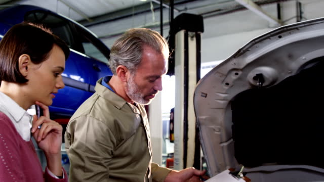 Mechanic showing customer the problem with car video