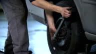 HD SLOW: Mechanic tightenes the screws on tires video