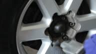 Mechanic tightens bolts of a car wheels video