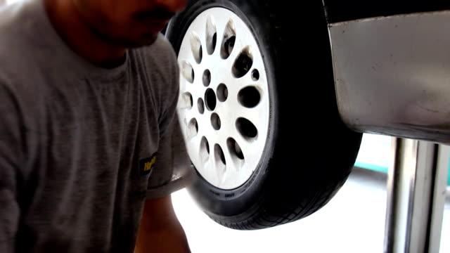 Mechanic tightens bolts of a car's wheels video