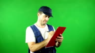 Mechanic using a clipboard in front of Green Screen video