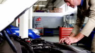 Mechanic using digital tablet while servicing a car engine video