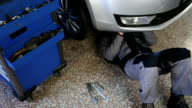 Mechanic working under the car video