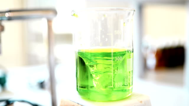 Mechanical stirring, liquid of green color is mixed in a round flask. video