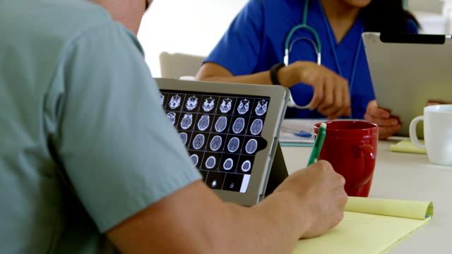 medical intern studies CAT scan images on tablet pc video