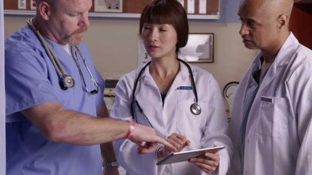 Medical professionals look at tablet video