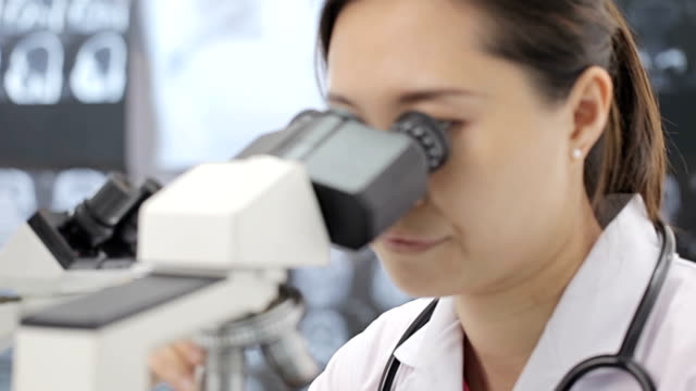 Medical researcher using microscope in laboratory video