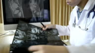 Medical staff examine x-ray video