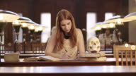 DS Medical student studying by observing a skull model in the library video