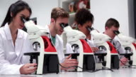 Medical students working with microscopes video