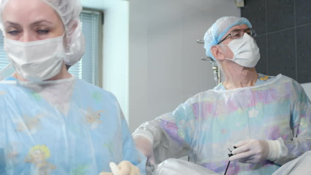 Medical team performing surgical operation in bright modern operating room video
