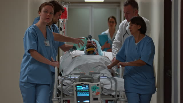 Medical team transporting a young male patient from the OR video