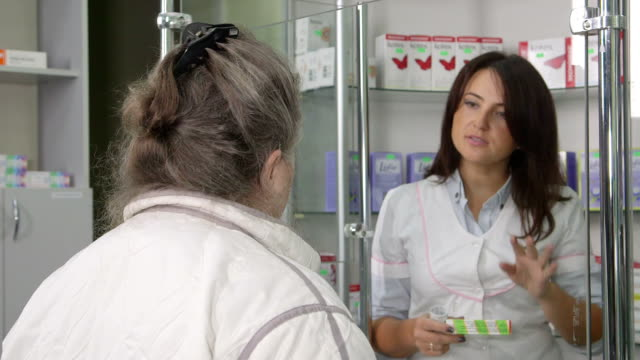 Medicines counter assistant giving advice to senior customer at pharmacy video