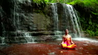 Meditating with Facial Painting in borneo rainforest waterfall video