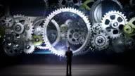 Medium Businessman standing big Gear wheels, connecting gear wheels. video